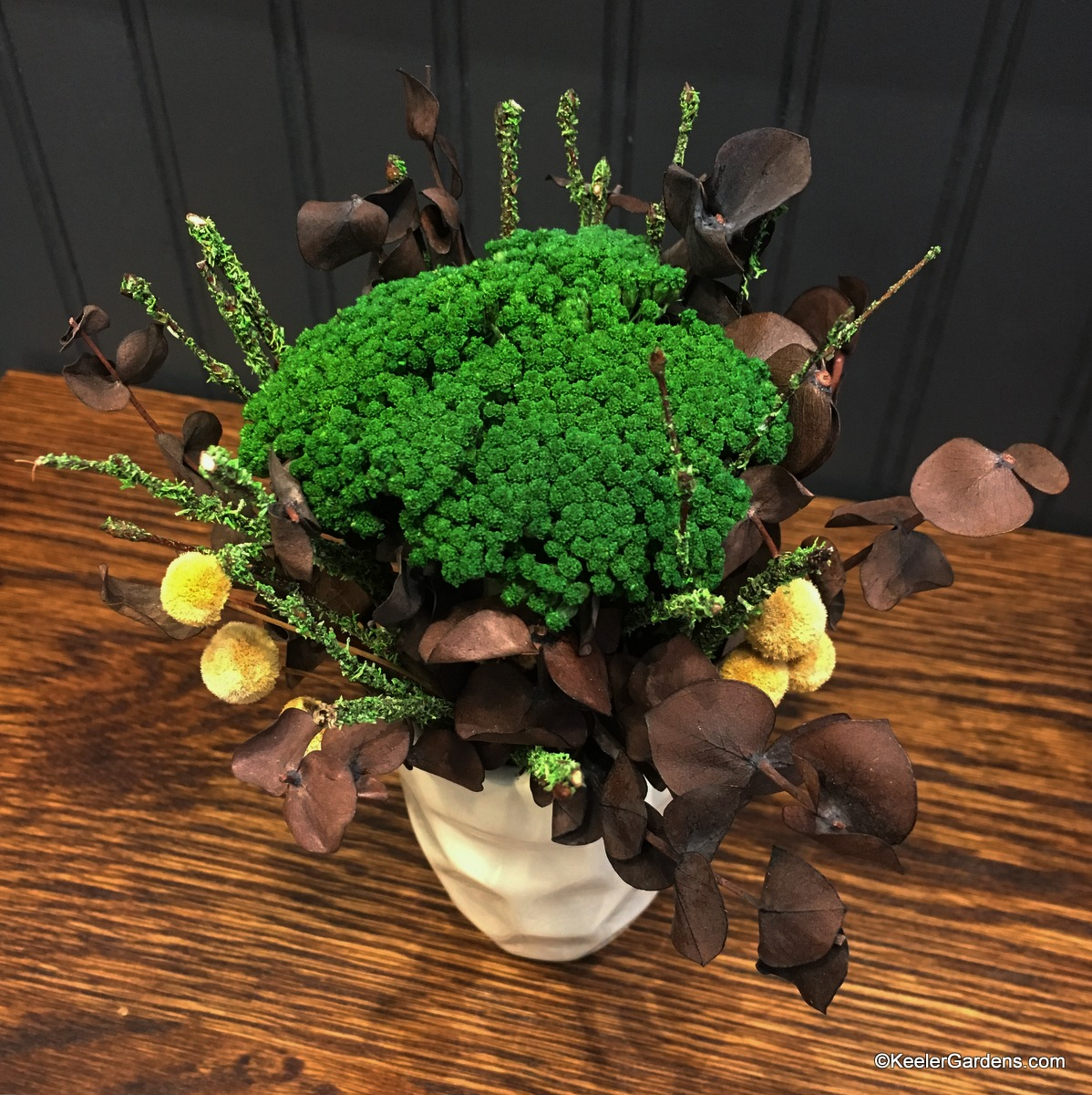 A sweet cluster of dried botanicals including green yarrow, chocolate-colored eucalyptus, yellow flower buttons, and green-flocked birch branches, all in a miniature off-white rippled vase.