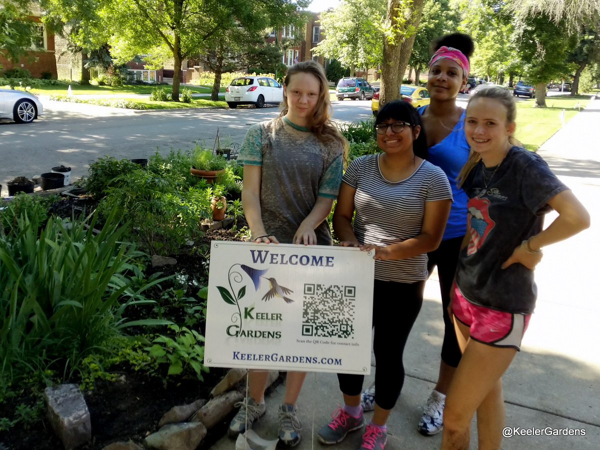"Four high school interns from across Chicago pose for a picture, standing in the right foreground in a group on a sidewalk with a sign that reads ""Welcome, Keeler Gardens."" In the background, mostly to the left, is the Keeler Gardens educational pollinator habitat, freshly planted, with a variety of Illinois native pollinator plants."