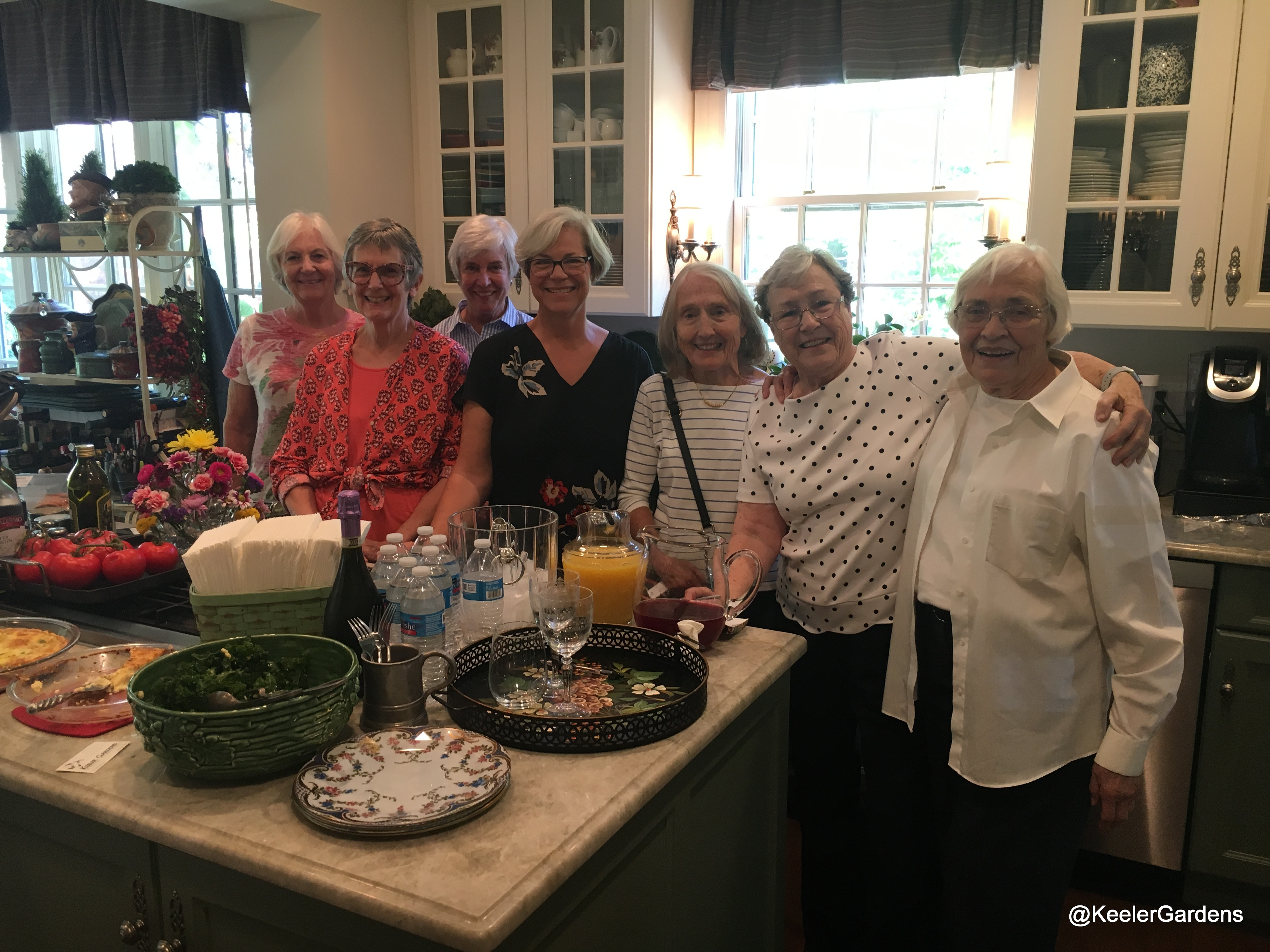 A group of ladies poses for a picture in a well appointed kitchen. On the island there is a bountiful display of food and beverage.